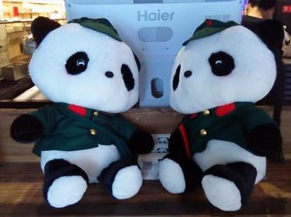 陶瓷的熊猫摆件,右手边的竹子上也是攀爬姿态的熊猫布偶.